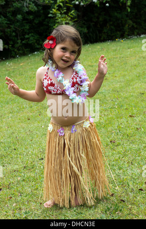 Little girl with Hawaiian Costume of hula dancer, Hula girl dancing outdoor in the garden over green grass barefoot. - Stock Photo