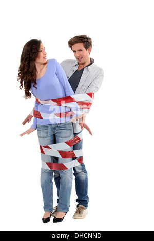 Couple being forcibly held together by caution tape - Stock Photo