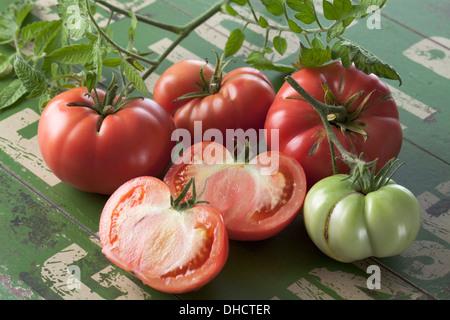 Whole and sliced Silesian raspberry tomatoes (Solanum lycopersicum), studio shot - Stock Photo