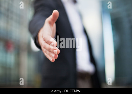 Businessman offering for handshake on office buildings background - Stock Photo