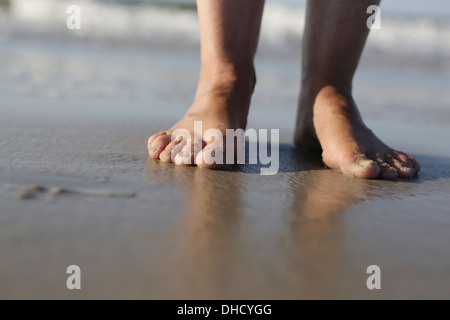 Germany, Lower Saxony, East Frisia, Langeoog, feet of a woman at the beach - Stock Photo