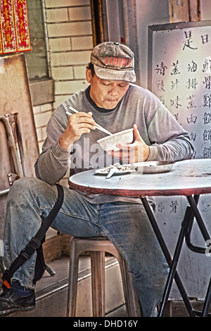 A male age 40-50 eating rice in a restaurant in Hong Kong. The image is a color photograph in portrait format. - Stock Photo