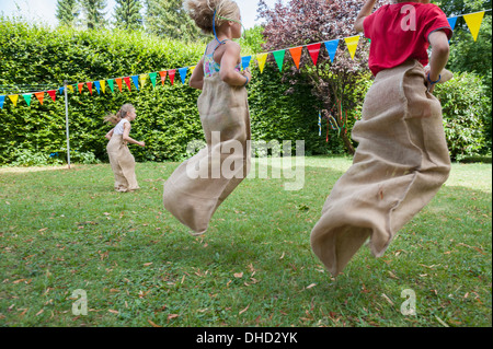 Children having a sack race in garden on a birthday party - Stock Photo