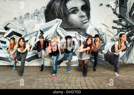 Germany, Stuttgart, Hall of Fame, Group of Hip Hop dancers at airbrush wall - Stock Photo