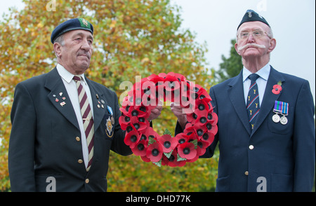 Two Second World War veterans stand to attention holding a wreath of Royal British Legion poppies by autumnal arboretum - Stock Photo