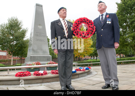 Two Second World War veterans stand to attention holding a wreath of Royal British Legion poppies beside a Dudley - Stock Photo