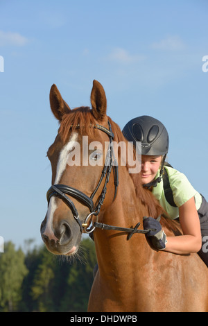 Thirteen-year-old girl wearing a helmet and a back protector on back of an Irish Sport Horse pony - Stock Photo