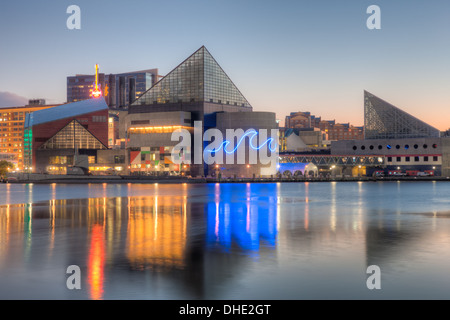 The Baltimore National Aquarium reflects off the waters of the Inner Harbor before sunrise in Baltimore, Maryland. - Stock Photo