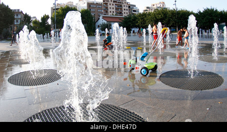 Kids refresh playing over floor fountains during a heat wave with temperatures around 40degrees in Mallorca, the - Stock Photo