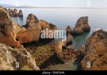 Weathered sandstone cliffs and sea stacks at Ponta da Piedade, Lagos, Algarve, Portugal. - Stock Photo