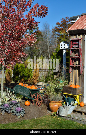 Autumn New England outside scene with pumpkins, plants and watering cans in front of wooden building. USA - Stock Photo