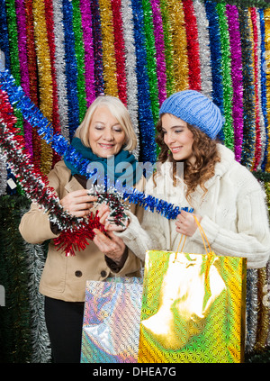 Mother And Daughter Selecting Tinsels At Store - Stock Photo