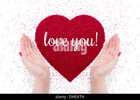 On the red heart made of sand written 'love you'. Nearby there are women's hands with red manicure. - Stock Photo