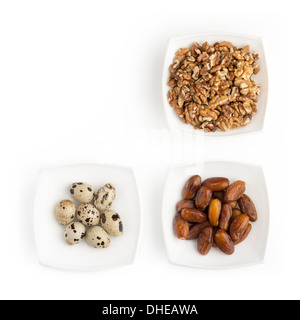 On the white table there are plates with walnuts, quail eggs and dates. - Stock Photo