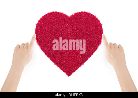 Woman's hands making the heart of red sand by index fingers on white background. - Stock Photo