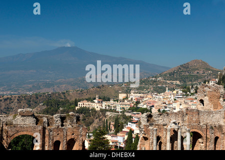 A view of Taormina from the Greek Theatre and Mount Etna smoking in the background, Taormina, Sicily, Italy, Europe - Stock Photo