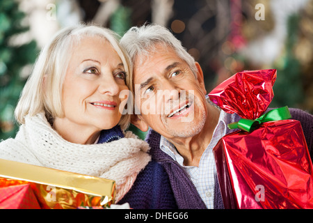 Couple With Christmas Presents In Store - Stock Photo