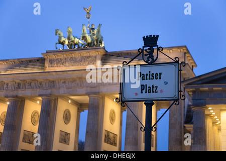 Brandenburg Gate (Brandenburger Tor) and Quadriga winged victory and road sign Pariser Platz, Unter den Linden, - Stock Photo