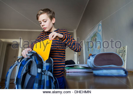 Schoolboy putting books in a schoolbag - Stock Photo