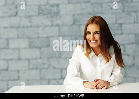 Laughing beautiful businesswoman sitting at the table in office - Stock Photo