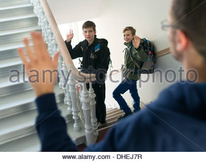 Children going to school and waving hands to their father - Stock Photo