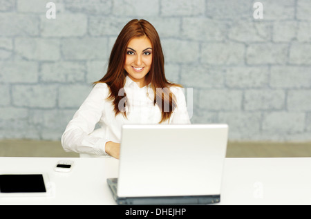 Confident happy businesswoman sitting at the table in office - Stock Photo