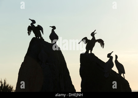 Cormorant statues on the seafront in Morecambe, Lancashire, silhouetted by the setting sun, part of the artwork - Stock Photo