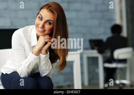 Portrait of a young happy businesswoman in office - Stock Photo