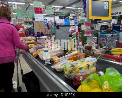 A woman at a checkout counter filled with groceries food in Co-Op supermarket Wales Britain UK  KATHY DEWITT - Stock Photo