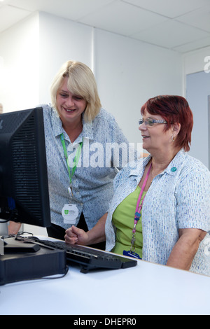 Hospital receptionists check appointments in an outpatient depatment UK - Stock Photo