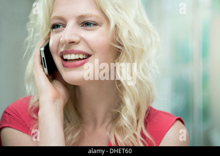 Young woman on cellphone, smiling - Stock Photo