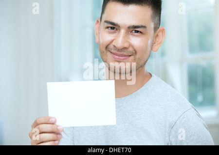 Mid adult man holding a blank card - Stock Photo