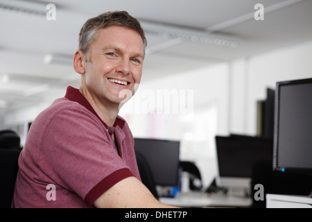 Man sitting at desk with computer, smiling at camera - Stock Photo