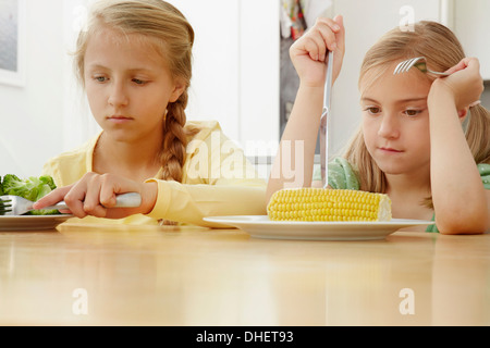 Girls poking vegetables on plate - Stock Photo