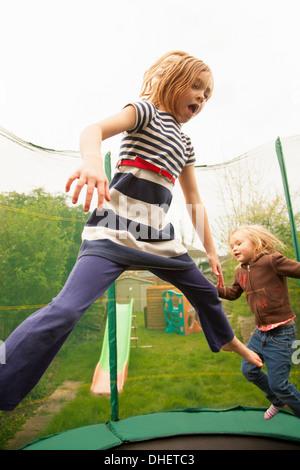Girls jumping on trampoline - Stock Photo