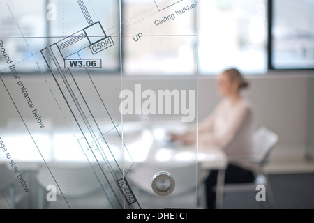Woman sitting at conference room table using laptop, view through window and architect plans - Stock Photo