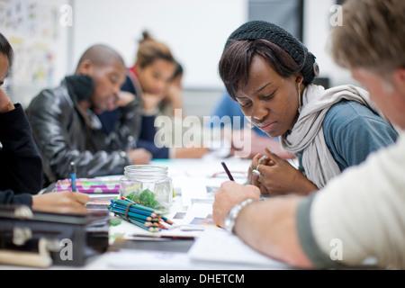 Tutor talking to woman in jewelry design class - Stock Photo