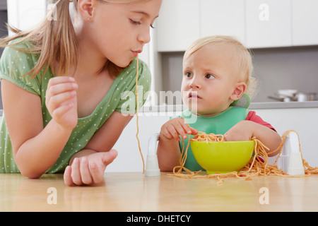 Girl and toddler playing with spaghetti