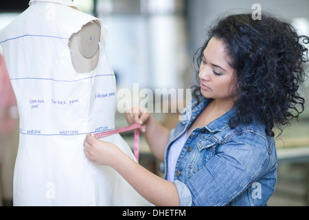 Fashion design student measuring in class - Stock Photo