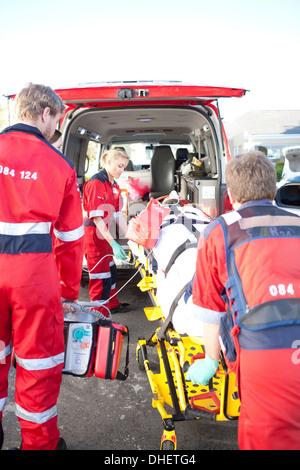 Paramedics lifting woman on stretcher into ambulance - Stock Photo