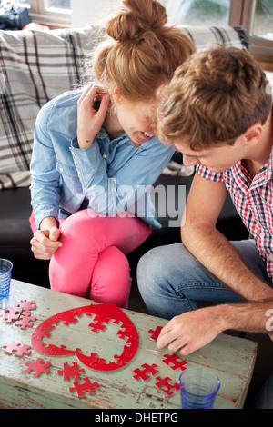 Couple doing heart shaped jigsaw - Stock Photo