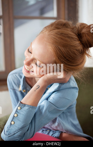 Young woman with question mark tattoo smiling - Stock Photo
