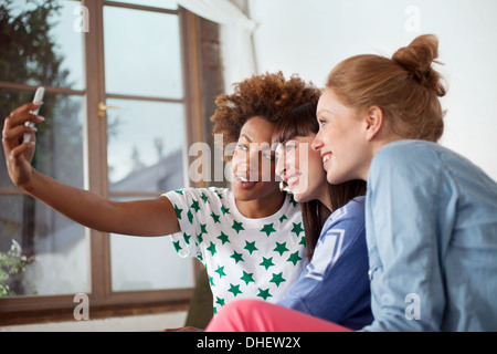 Three female friends photographing themselves with camera phone - Stock Photo