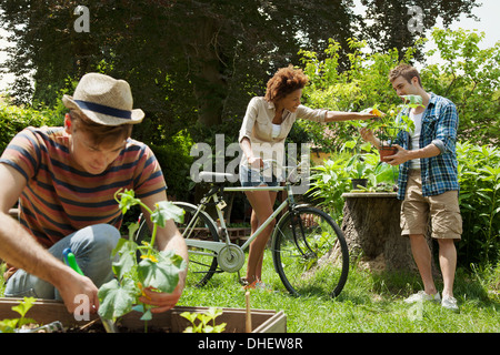 Friends gardening, woman with bicycle - Stock Photo