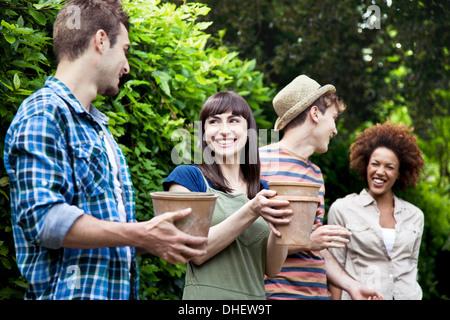 Four friends holding terracotta plant pots - Stock Photo