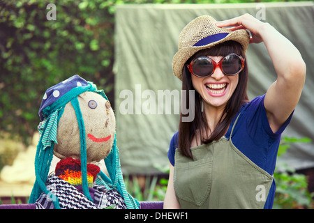 Woman wearing sunglasses and hat with scarecrow - Stock Photo