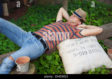 Young man wearing straw hat lying on sack - Stock Photo