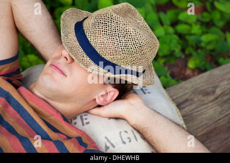Young man wearing straw hat with hands behind head - Stock Photo