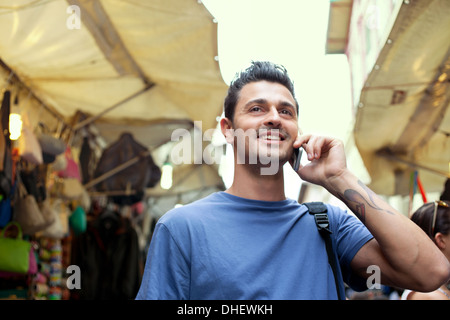 Young man on cell phone, San Lorenzo market, Florence, Tuscany, Italy - Stock Photo