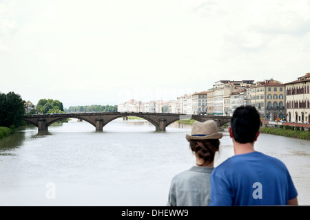 Couple looking at Ponte alle Grazie, Florence, Tuscany, Italy - Stock Photo